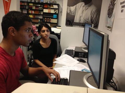 """Double Discovery Center senior Jeremy Luna working with DDC volunteer Rubab Rehman '15 on a college scholarship application. Rehman worked with the Center's """"Scholarship Saturdays"""" program,which assisted high school seniors with researching scholarship opportunities and drafting their essays. Photo: Lisa Herndon"""
