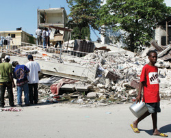 People sift through the rubble in downtown Port-au-Prince, seeking to salvage usable building materials and personal objects.