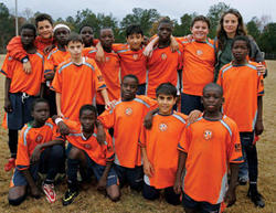 Luma Mufleh (back row, second from left) founded the Fugees in hopes that soccer would help unify the refugee children who settled in Clarkston, Ga. PHOTO: Nicole Bengiveno/The New York Times/Redux