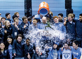 Head coach Michael Aufrichtig (wearing glasses) receives a celebratory soaking after Columbia's men's and women's fencing teams won 2014 Ivy League Round Robins. Photo: Columbia Athletics/Mike McLaughlin