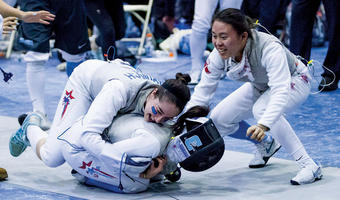 Jackie Durbovich '16 and Margaret Lu '16 rush the mat to hug Sara Taffel BC'17 after a victory in foil. Photo: Columbia Athletics/Mike McLaughlin