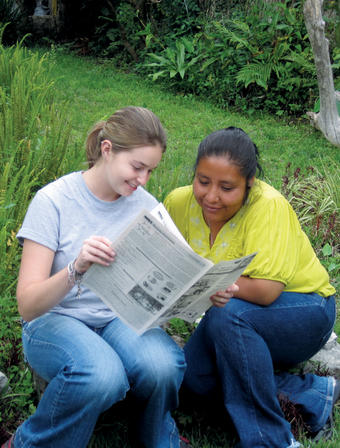 Rebecca Pryor '09 (left), with Marta Lidia Garcia, reads a newspaper published by Community Enterprise Solutions near CES' Antigua, Guatemala, office. Pryor began her work with nonprofit CES as an intern and now is a full-time project manager.