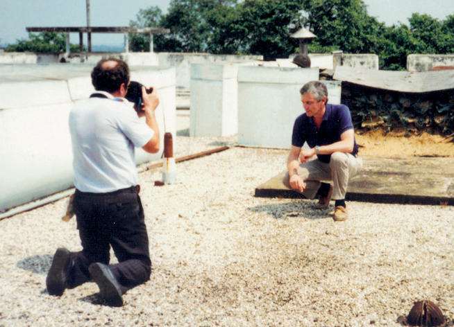 A BBC TV crew member films Snepp in 1991 on the roof of the U.S. Embassy in Saigon for a documentary. PHOTO: COURTESY FRANK SNEPP '65, '68 SIPA