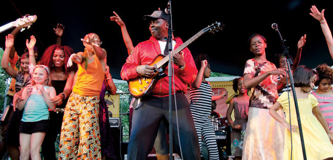 Audience members join Diblo Dibala on stage during a Congo Square New World Rhythms Festival. PHOTO: COURTESY NEW ORLEANS JAZZ & HERITAGE FOUNDATION/ERIC SIMON