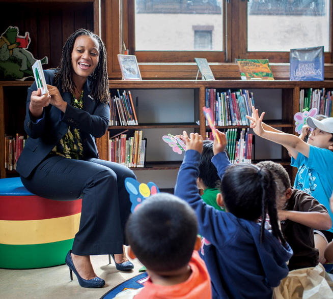 Sheena Wright '90, '94L reads The Hungry Caterpillar during a United Way program at the Mott Haven Public Library in the Bronx. PHOTO: NATALIE KEYSSAR