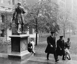 Two ROTC students in dress uniform pass by the statue of Alexander Hamilton in this historical photo, date unknown.