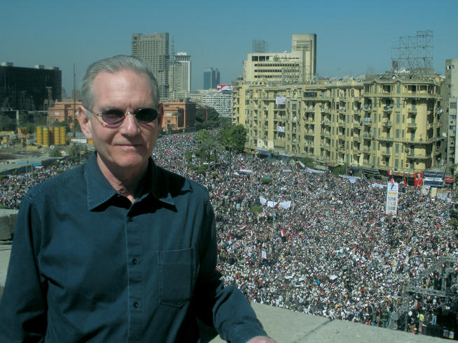 "Marc Rauch '69 stands atop the fifth story roof of the AUC Science Building, which fronts directly on Tahrir Square, where a crowd estimated at more than one million gathered on ""Victory Friday,"" February 18. Photo: Sean Graham"