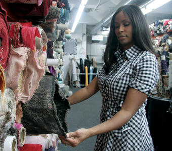 Sharene Wood '94, CEO of 5001 Flavors, browses fabrics at Mood in Manhattan's garment district while wearing one of her company's dresses. PHOTO: KAREN KELLER '05J
