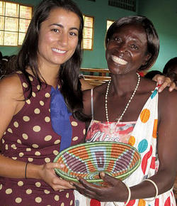 The president of a local women's cooperative in the Muhanga district presents Neda Navab '08 with a handmade basket as a token of thanks at the training program graduation ceremony.