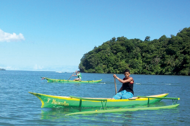 Two villagers paddle new MicroAid canoes across Lefaga Bay. Photo: John Ross '83