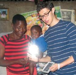 Lit! Solar founder Ben Hirschfeld '16 with lantern recipient Doreen Acheing in her home in Kibera in the Kenyan capital of Nairobi. Photo: Jeff Okoth