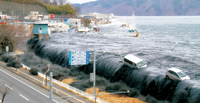 The tsunami, measured at one location at 128 feet, washes away cars as it approaches Miyako City. PHOTO: HITOSHI KATANODA/POLARIS