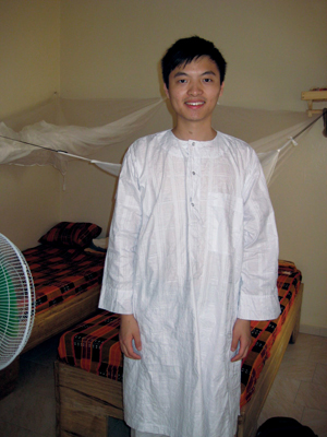 Thomas Sun '11, shown here in his bedroom in Senegal wearing a traditional Senegalese outfit, has been connecting Harlem families with essential resources through Project HEALTH since his first year at the College. PHOTO: TRELL MALVEO
