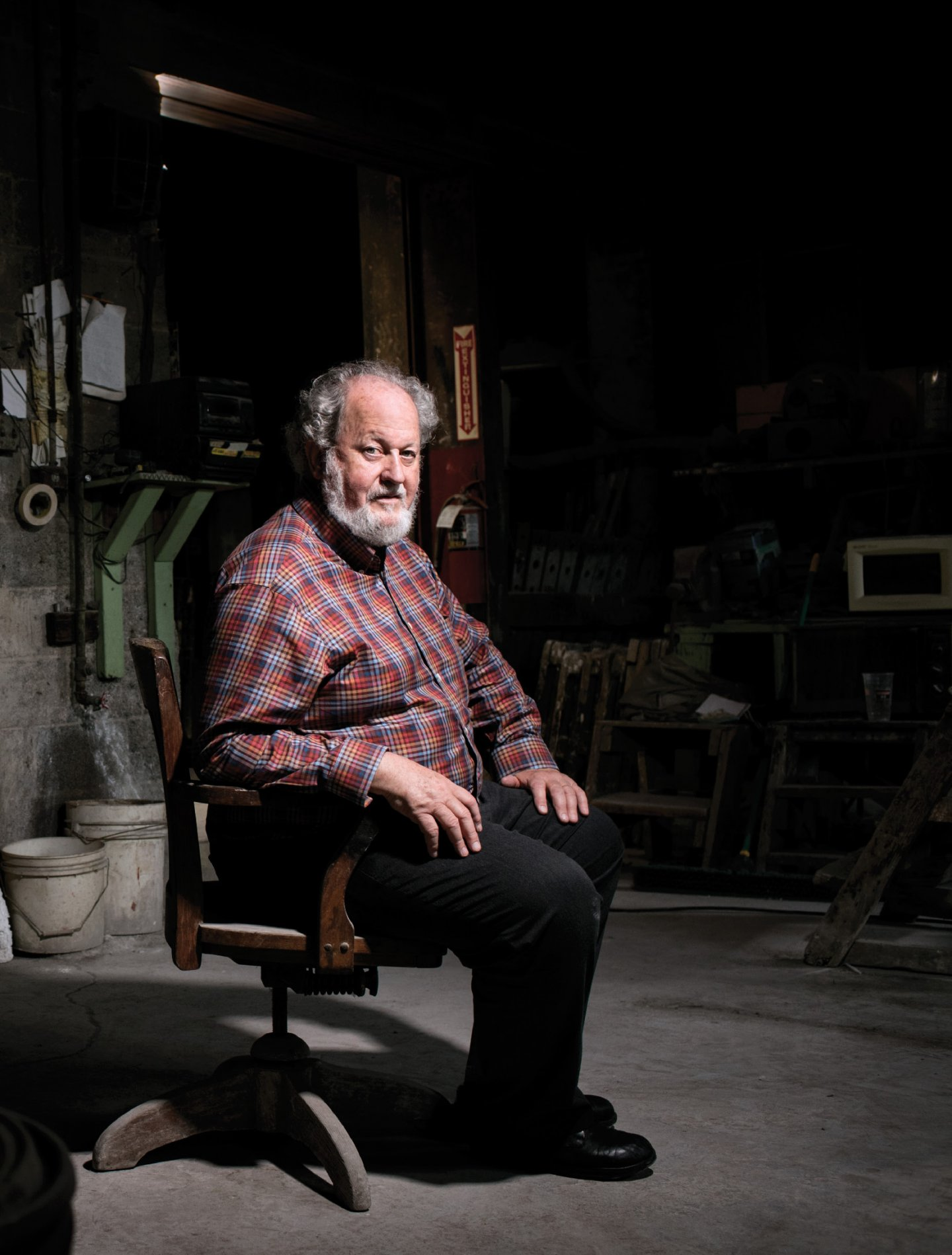 A bearded man in a checked shirt sitting in a dark room