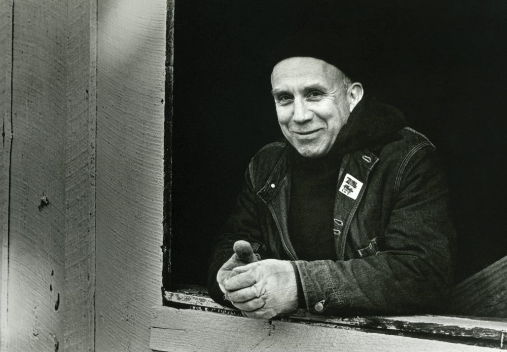 a smiling man leaning on an open windowsill