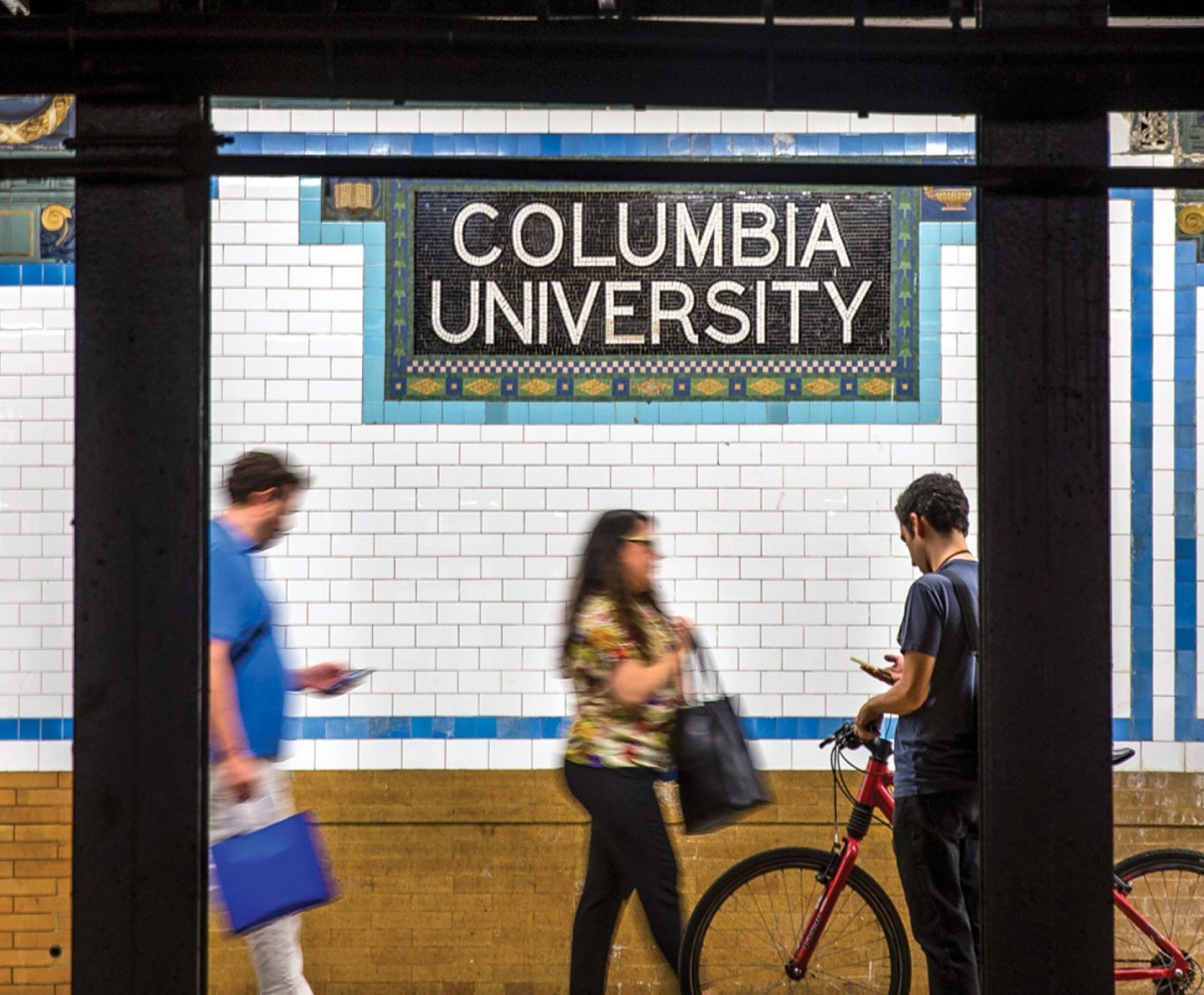 "Subway platform for the number 1 train stop at Columbia University, showing a tiled wall containing a mosaic spelling ""Columbia University""."