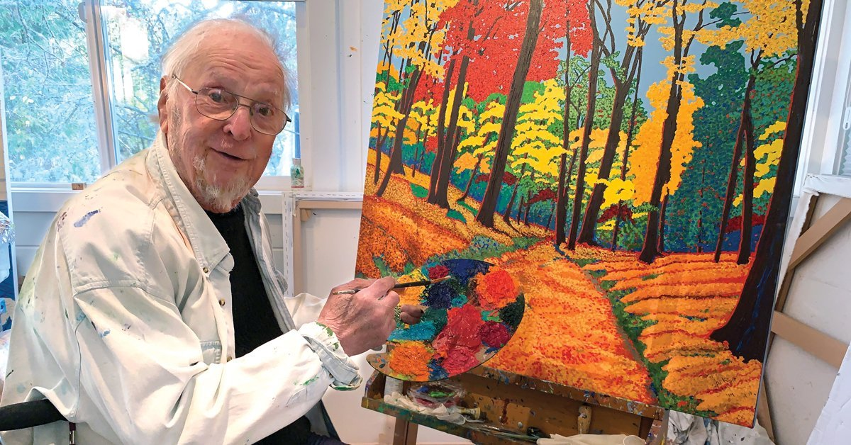 Jack Stuppin '55 seated in front of an unfinished painting, holding a paintbrush