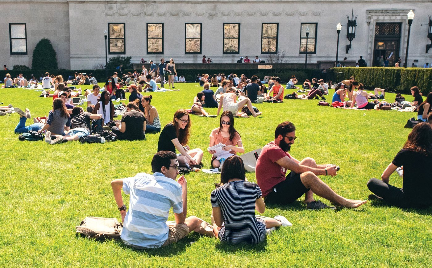 Many students seated on a grassy lawn on the Columbia University campus