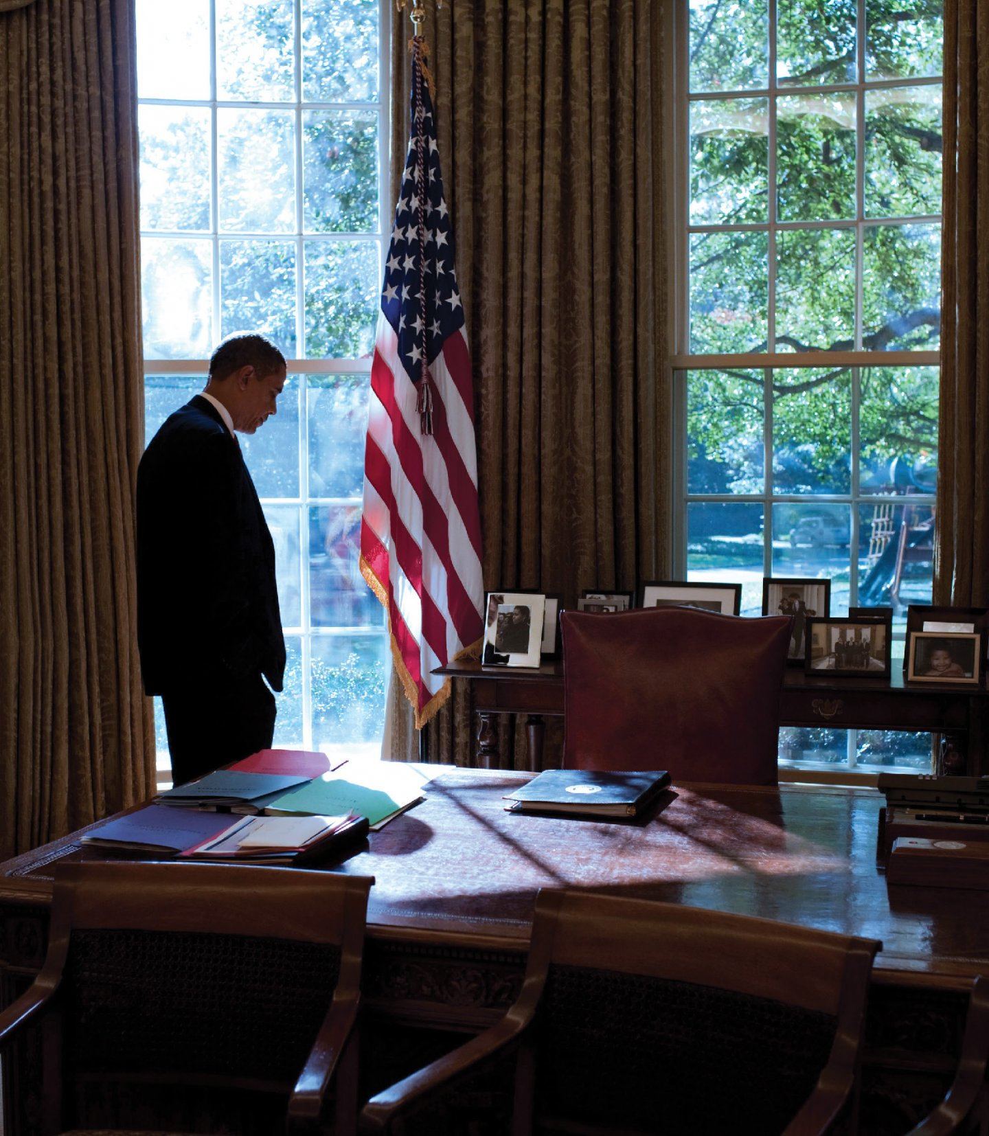 Barack Obama in the Oval Office, an American flag hanging nearby