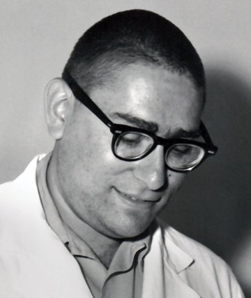 a man in glasses looking downward