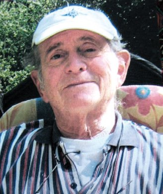 An elderly white man in a baseball cap smiling
