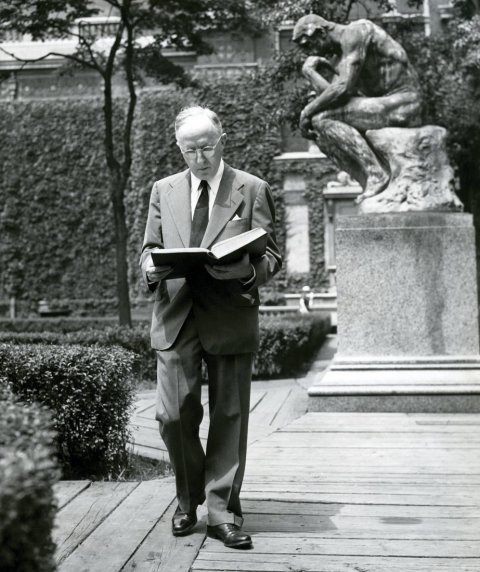 A man wearing glasses, reading a large book while walking.