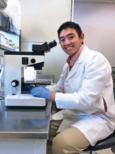 A young Asian man in a lab coat smiling while sitting at a microscope