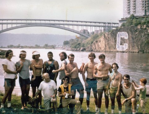 A group of young men on the bank of a river.