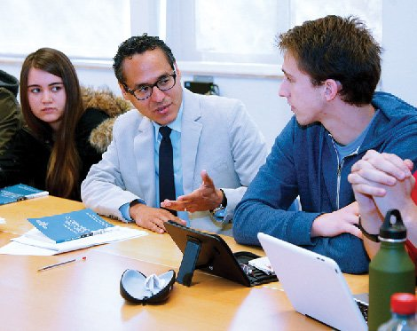 A man talking to students around a seminar table