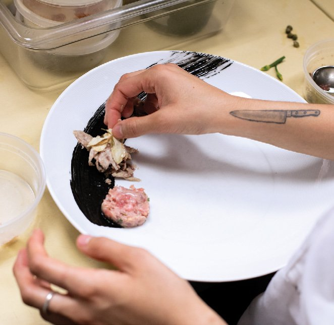 A chef prepares a black garnish on a plate.