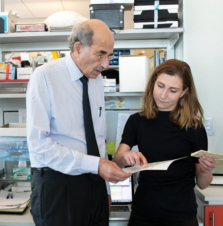 an elderly man and a young woman looking at a paper in a lab