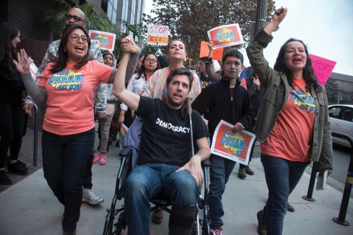 a man in a wheelchair surrounded by activists