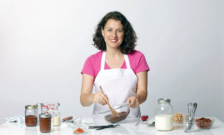 a woman in a pink shirt and apron, stirring chocolate in a bowl