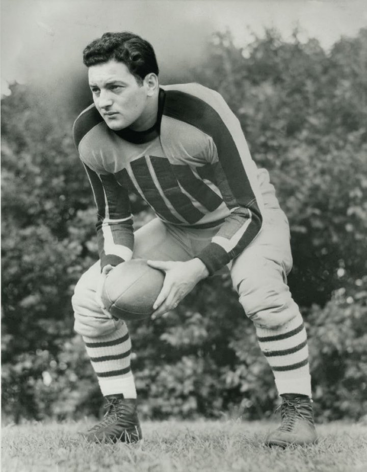 Sid Luckman '39 in a football uniform holding a football