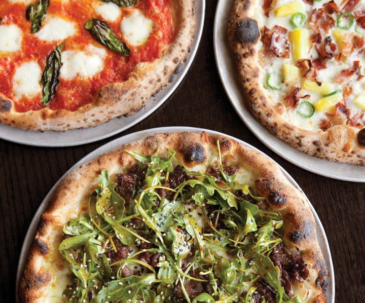 Three pizzas in dishes on a wooden surface