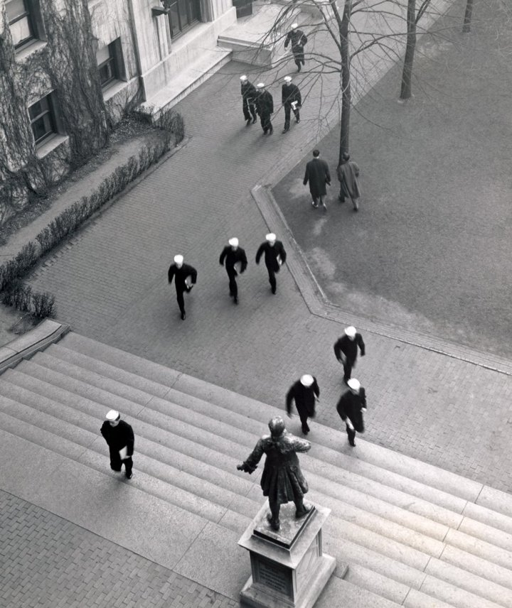 Several men walking on the Columbia University campus, a number of whom are  wearing dark uniforms and light-colored hats.