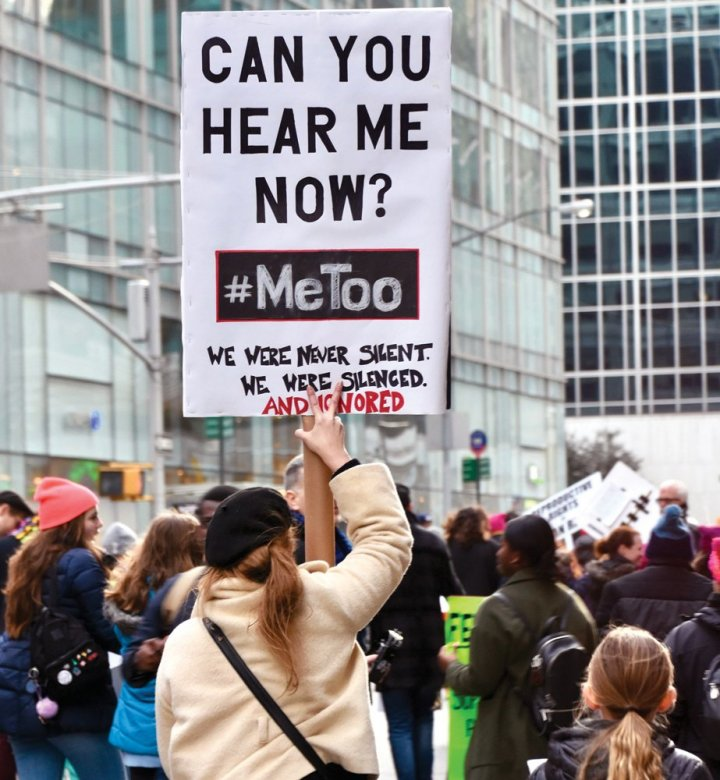 """Several people outdoors in front of tall buildings holding signs, one of which contains the words """"Can you hear me now? #MeToo."""""""