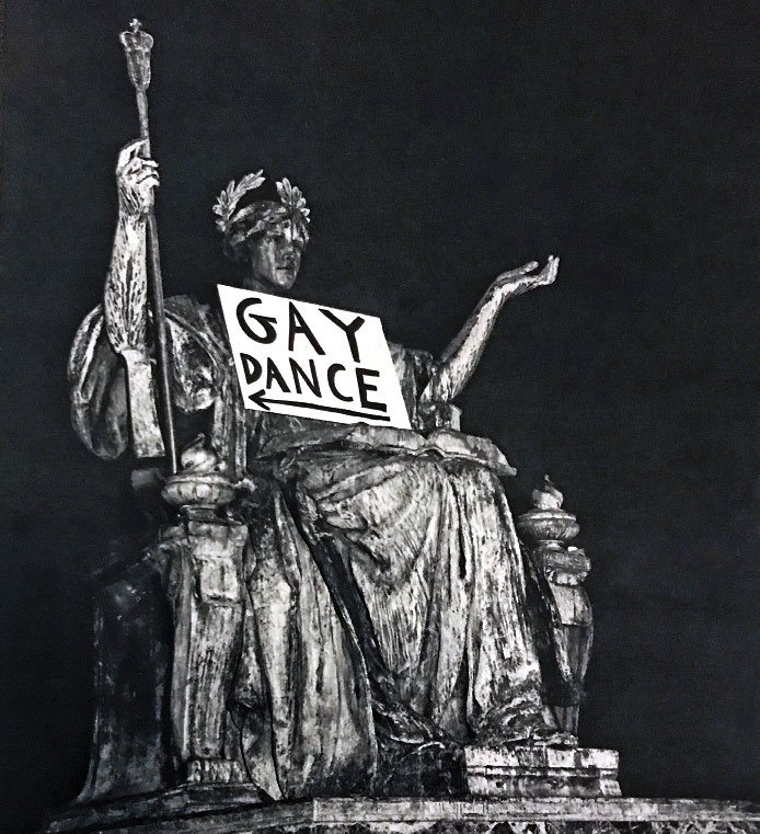 """A sign labeled """"Gay Dance"""" rests on the lap of the Alma Mater statue on Columbia's campus."""