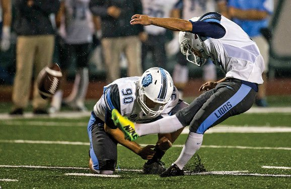 A Columbia Lions football player kicks the football into the air.