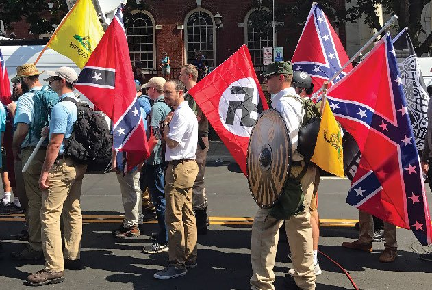 a crowd of white men holding Nazi and Confederate flags