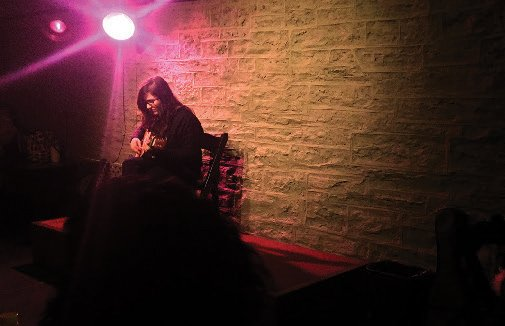 A woman playing a guitar under a pink light