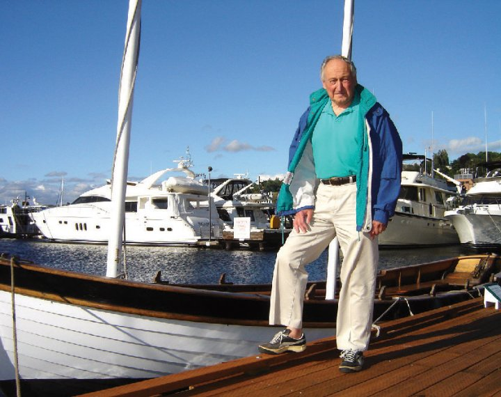 A man posing in front of a docked boat