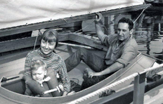 A black and white photograph of a young family on a boat