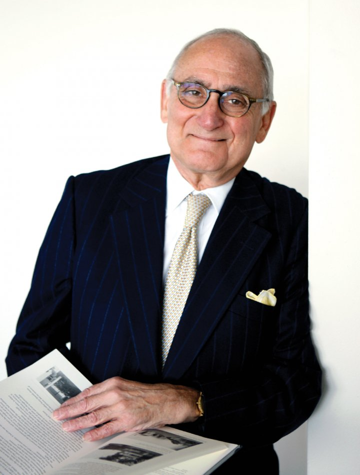 A white man in glasses and a suit and tie, with a yellow pocket square