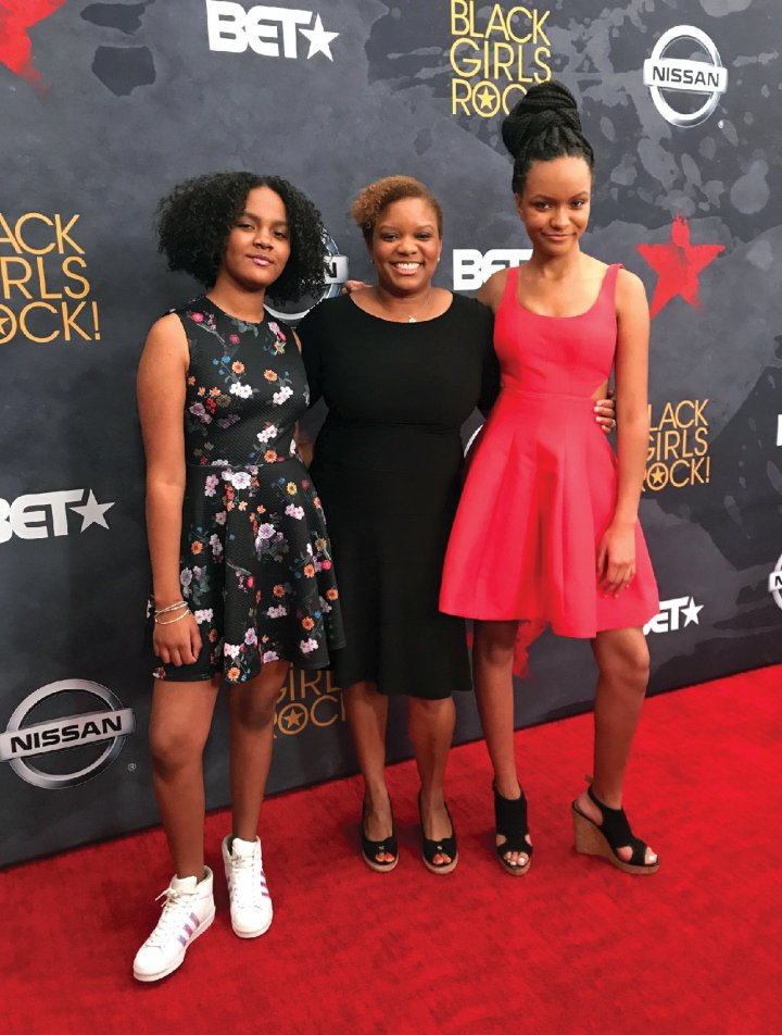 three black women on a red carpet