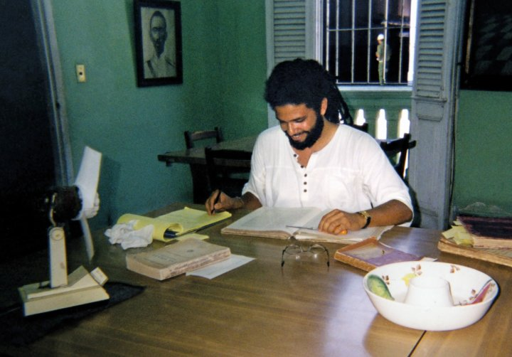a man with a beard at a table with books