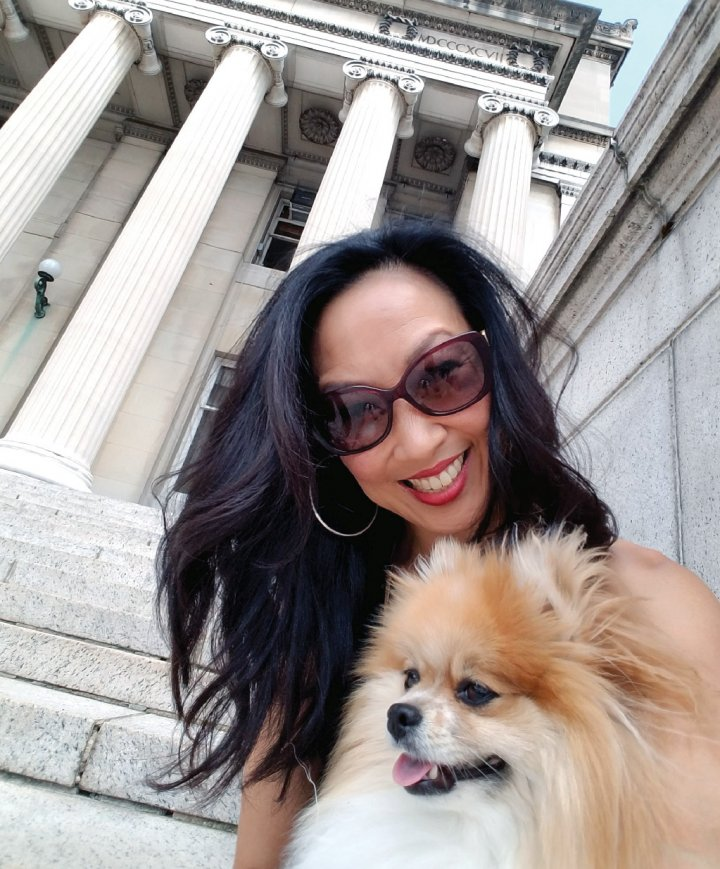 a woman in sunglasses and a Pomerian dog