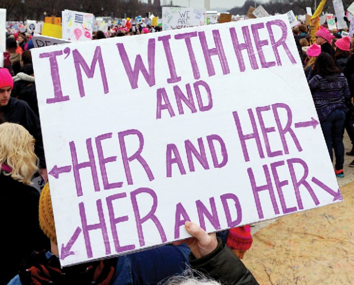 """A sign reading """"I'm with her and her and her and her"""""""