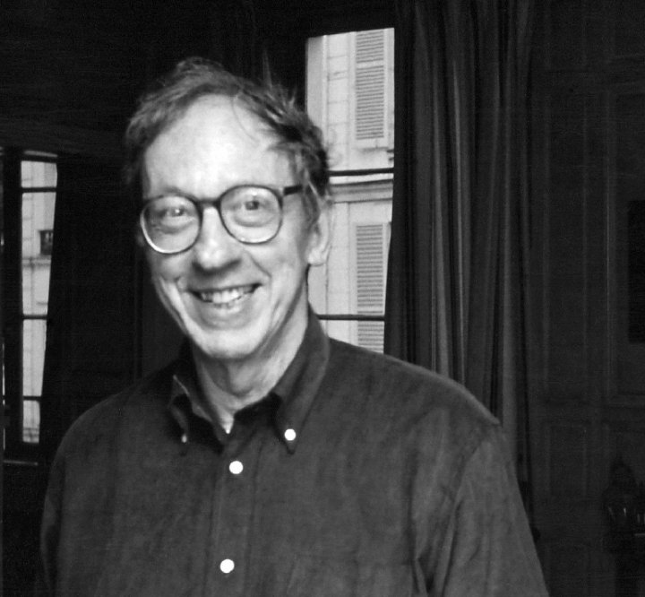 a blurry black-and-white photo of a man wearing glasses