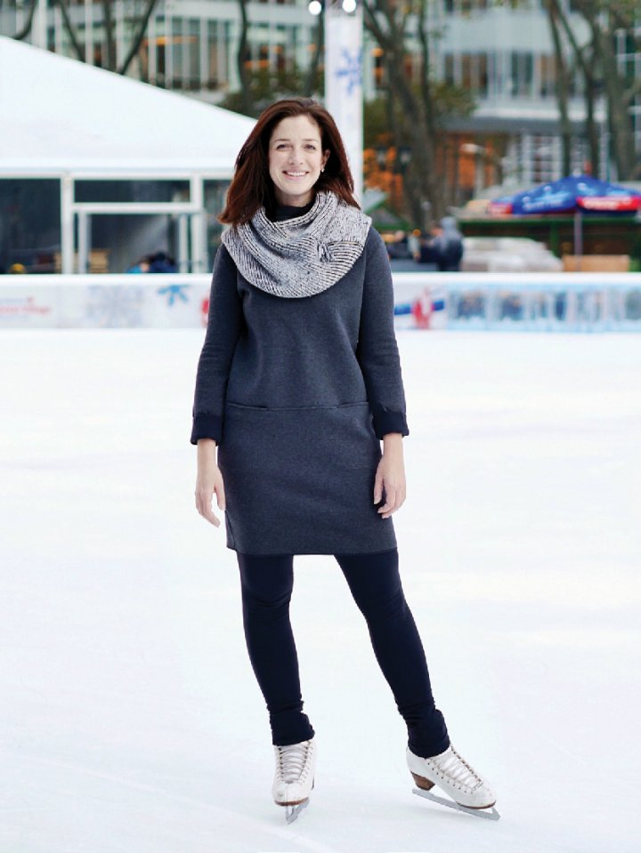 A woman standing skates on an ice rink